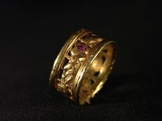 This gold love token ring from the 16th century is decorated with clasped hands and hearts. Each heart is set with an uncut ruby.
