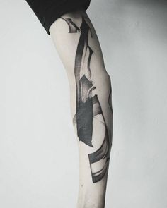 Brush stroke-like abstract tattoo on the right arm.