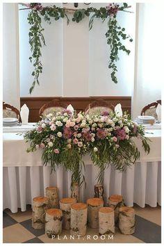 Na białym tle inicjały w kolorze przewodnim. na pniach przed stołem słoje ze świecami (ozdobione) w kolorze przewodnim