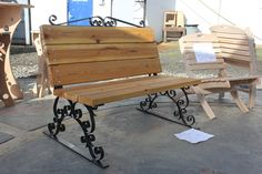 Garden bench with cedar boards and custom ornamental steel feet and back hand-wrought and constructed by SHS welding students.