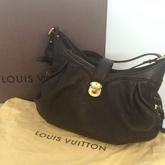 """Louis Vuitton Chocolate Monogram Mahina XS Bag It features a feminine and chic slouchy look with intricate very dark brown calfskin perforated monogram and a spacious interior.Only the tiniest sign of wear on the front seem (pic)which is not visible unless looking for it, some extremely light wear to buckle (pic),zip tab.  Measurements: 15.5"""" L x 7"""" W x 10.5"""" H Interior: One flat pocket, one cell phone pocket, microfiber lining Handle Drop: 15.5"""" - 17.5"""" adjustable Single zip top with flap…"""