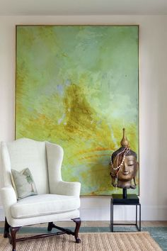 large painting behind white arm chair and buddha statue