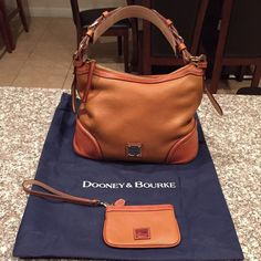SOLD--Dooney & Bourke Used Dooney & Bourke cognac (it just looks orange in the pics) handbag in good condition. Comes with matching zipper pouch. Also comes with dust bag.  Side note... This bag has several compartments inside and a zipper compartment on the back too. This is a MEDIUM sized bag. I LOVED this bag... So much that I purchased 2 of them. ‼️I have additional pictures listed‼️ Dooney & Bourke Bags Shoulder Bags