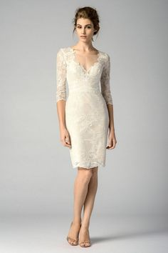 Watters Encore 7201E Mango Bridesmaid Dress. The dress is overlaid with floral lace and accented with tulle paneling along the yoke and back. Sheer three-quarter sleeves frame the illusion V-neckline, arrayed with irregular scallops. Tapered through the thighs, this lacy ensemble then finishes with a knee-length pencil skirt, adorned with a center-back kick pleat.