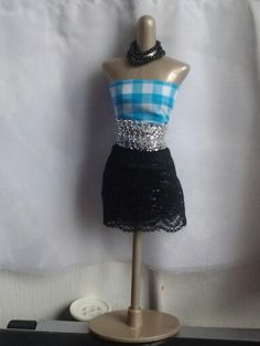 Harumika design #2: this is a blue and white checked top with a black lace skirt and a silver netted belt.