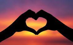 Handen van hem en van haar vormen samen een hart met daarin de ondergaande zon