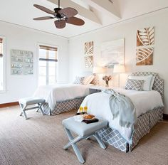 Tropical island bedroom with twin headboards upholstered in gray lattice fabric, gray lattice bedskirts & pillows, white bedding with turquoise blue trim, gray x-bench ottomans with nailhead trim, gray throws, West Elm Parsons Console Table nightstand, wood leaf art and sisal rug.