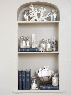 Coral and glass jars filled with sand and shells from your beach vacations create a summer still life and beach memories in a bookcase. Coral branch shown available at http://www.seasideinspired.com/0262_resin_coral.htm