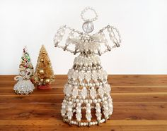This vintage safety pin and bead angel would make a nice tree topper.