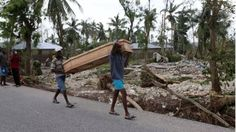 Men carry a coffin after Hurricane Matthew hit Cavaillon, Haiti, on 6 October 2016.