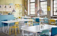 Kaviareň s bielymi stolmi v kombinácii s rôznymi žltými, tyrkysovými, bielymi a modrými stoličkami.