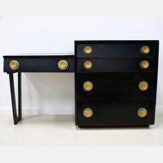 Dating to the 1940s or '50s, this wood dresser is painted in sleek black and features oversized, circular brass-colored knobs. This unique design pairs a dresser with an attached vanity