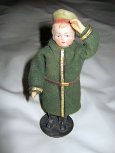 """- Candy container doll soldierwith lovely antique bisque head - Size : 5.5 """" Painted face - Pressboard body forest green felt uniform with golden stripes. Hands are composition and fixed with wires -"""