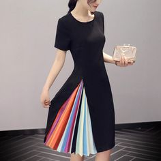 Short-sleeved black dress with round neck has high, off-center slit with rainbow-colored pleated inset.