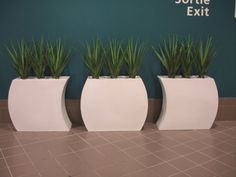 White curvy barrier planters planted with artificial plants