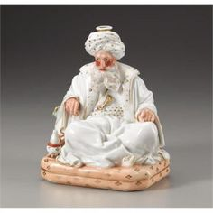 A Jacob Petit Figural Porcelain Scent Bottle~In the form the form of a Sultan~seated with legs crossed on a cushion~Wearing a gilt enriched turban~Elbow resting on another cushion~Hookah at his side~Circa 1840