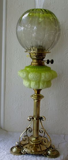 antique english victorian oil lamp with poppy etched clear to light green shade and floral pattern pressed glass multi shaded green opalescent font. With double burner.