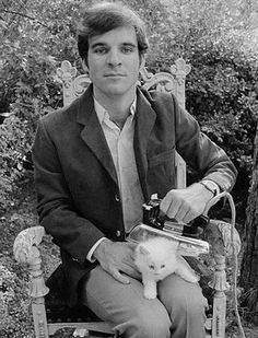 American actor, comedian, author, playwright, producer, musician and composer Steve Martin grooming his kitten