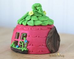 A whimsical fairy house to attract a fairy to your garden! This little pink fairy house yellow flowers, windows to peek inside, and itty bitty pots on the window sills! This is the home of the Fairy D