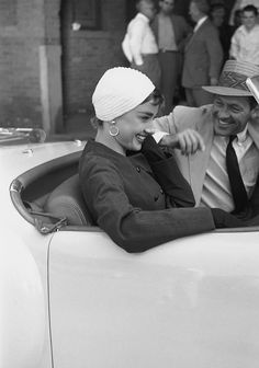 1953. New York. Actors Audrey Hepburn and William Holden in a Nash-Healey roadster on the set of director Billy Wilder's film, 'Sabrina' . Hepburn is wearing a skirt suit and hat designed by Hubert de Givenchy.  Photo by ?