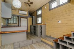 The Dutch door (which also has a doggy entrance) lets you into a living area to the side of commodious storage stairs leading up to a sleeping loft.#TinyHouseforUs