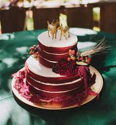 rustic deep red naked wedding cake with gold deers cake toppers