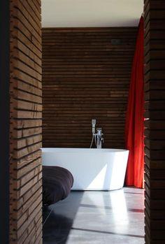 Bathroom with wooden wall, concrete colored tiles, a moderne white bath tub and a red curtain | Salle de bain avec des murs en bois, du carrelage couleur béton, une baignoire moderne blanche et un rideau rouge.