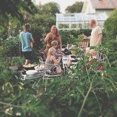 Echanges autour de la table d'hôte dans un jardin vert à proximité du potager de la famille. Repas champêtre avec un joli mobilier de jardin en fer forgé.
