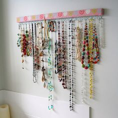 Necklace organizer ---thin wood strip covered in fabric-(modge podge?)- eye hooks - affix (nail?) onto wall