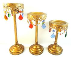"""Gold Christmas Holiday Colored Crystal Ornate Candle Holders by Opulent Treasures. $94.99. Measurements Small: 9"""" (Height). Measurements Tall: 13"""" (Height). Measurements Medium: 11"""" (Height). Take a look at these beautiful antique-style candle holders by Opulent Treasures These gorgeous pieces have multi-colored glass teardrop beads that hang from each candle plate You can use the holders with taper candles or a 3"""" thick pillar candle Used best to decorate your home or table fo..."""