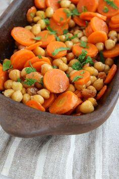 Cenoura e grão de bico assados com cominho Ingredientes 2 cenouras (cortadas em fatias com 0,5cm de espessura) 1 dente de alho (bem picado ou espremido) 1 xícara de grão de bico (cozido e drenado) 1/4 xícara de passas claras 1/2 colher (chá) de cominho em pó 1/4 colher (chá) de sal 1 colher (sopa) de azeite de oliva 1/2 xícara de caldo de vegetais Arroz integral cozido (ou cevadinha)