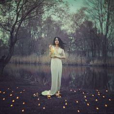 Девушка в длинном белом платье стоит со свечей в руках, фотограф Anita Anti