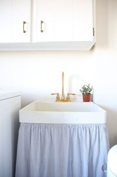 Utility sink in a laundry room gets a cute skirt eclecticallyvintage.com