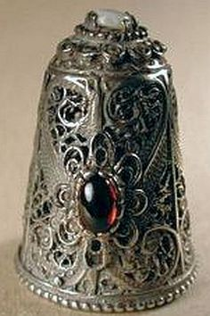 Spanish cast silver thimble has a small opal on the top and a mounted garnet on the front.