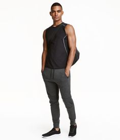 20  Light gray melange. Sports pants in thick jersey with an elasticized drawstring waistband. Side pockets with zip, tapered legs with seams at knees, and wide