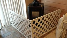 Diy hinged baby fence for freestanding stove. Used vinyl lattice and shelf brackets for feet. Cost less than $40.