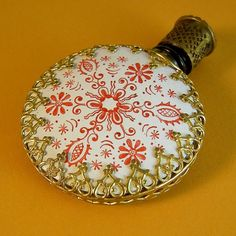 Circa 1930, the front panel of this miniature bottle is shielded by a crisp white enamel plate that has a red lacy, snowflake- or starburst-type decorative pattern, with alternating spokes of finely painted flowers and ornamental buds. The bottle's back shows a bare pressed glass panel with a raised spirograph-type decoration. A gilt metal filigree frames the bottle edges, with a heart-shaped filigree edging that folds into and points to center on the bottle's side panels.