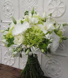 White and green bridal bouquet includes hydrangea, lisianthus, roses, sweet pea, freesia and oregano!