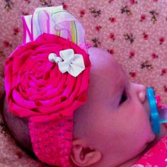 Pink satin rolled flower clipped to a crocheted headband. I glued some felt to the underside of the headband so the clip wouldn't press or scratch on baby's delicate skin. You can change out clips for versatility.