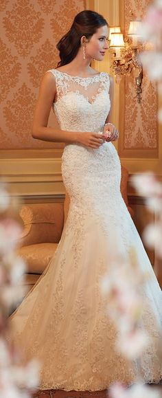 This lace sleeveless wedding dress by Sophia Tolli features a sheer tulle bateau neckline and scattered crystal hand-beading over a sweetheart bodice.