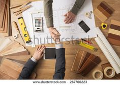 Architect and customer businessman shaking hands top view, desktop with building project, tools and wood swatches on background - stock photo