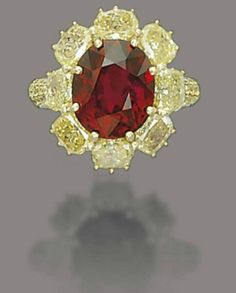 """Burmese red ruby and yellow diamond ring.  This important piece features an oval ruby weighing 8.11 carats, sourced from Burma. The ruby is a uniform and highly saturated """"pigeon blood"""" red with no signs of heating or enhancement. It is surrounded by yellow diamonds on a size 6 gold ring."""