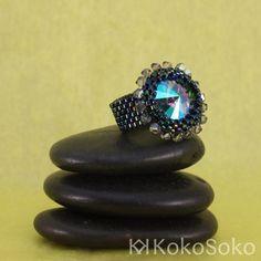 Diseño con cristal de Swarovski que cambia de colores con la luz y con cristal japonés azul oscuro tornasolado, rodeado de una corona de tupis Swarovski.