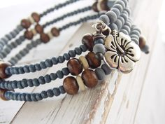 Incredibly lightweight, this bracelet is a perfect addition to your casual layered bracelets. Light and dark denim blue, brown and cream wood beads are placed in a consistent pattern, creating the illusion of 3 matching bangles. In reality, this bracelet wraps around the wrist and