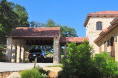 Stone carport with clay tile roof at the entry to this lakeside Mediterranean style home.