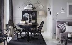 Comedor mediano con una mesa de comedor redonda negra, cuatro sillas de ratán y una vitrina también negra.