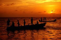 Fishermen waiting to pull nets in as sun sets over Caribbean Sea. Cartagena, Colombia.