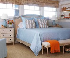Perfect decor for a beach bedroom.  Woven wood shades on the window behind the bed.