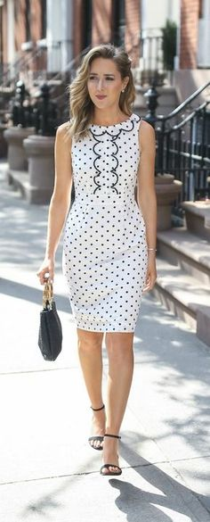 White knee-length shift with black polka dot print. Slightly high defined waist. Vertical panel in the middle of the bodice outlined in black scalloped piping. Scalloped collar in same black piping. Dips to a vee in the back. Black bag, black ankle strap sandals. Ladylike. Style Planet