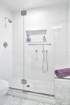 The gray and white color palette in this contemporary master bath gives the room a clean, airy feeling. A frameless glass enclosure keeps the streamlined shower in view, and white subway tile is accented by gray mosaic tile on the floor and inside a functional niche. White marble surrounds the shower, and floor tile is laid in a tight herringbone pattern for added interest.